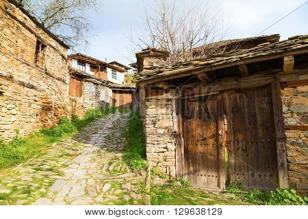 Village of Leshten Bulgaria. Entrance driveway to a rustic stone house with old outbuildings with weathered wooden doors and the house in the background.