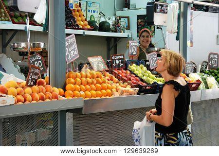 MALAGA, SPAIN - JULY 11, 2008 - Customer being served at a fruit and veg stall in the indoor market (Mercado de Atarazanas) Malaga Malaga Province Andalucia Spain Western Europe, July 11, 2008.