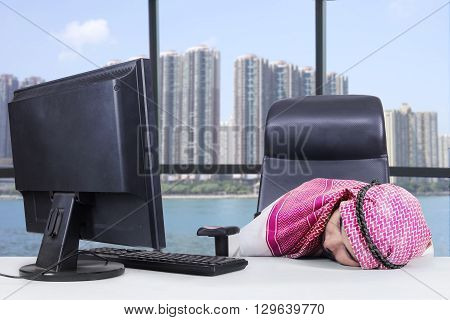 Tired middle eastern worker wearing headscarf and sleeping in the office with computer on desk