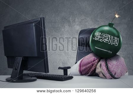Frustrated muslim businessman sleeping on the table with Arabian flag on the bomb above his head