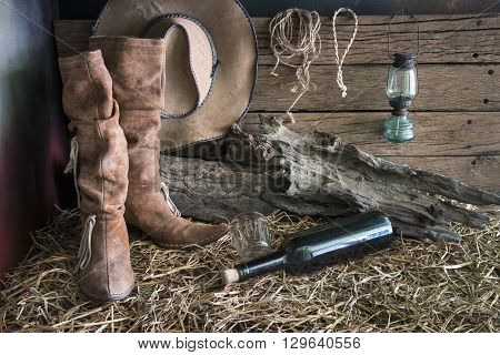 Still life painting photography with traditional leather boots and american west rodeo brown felt cowboy hat in vintage ranch barn background