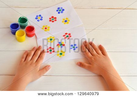 Two paintings of flowers painted children fingers. Jars with gouache. Children hands are on the table