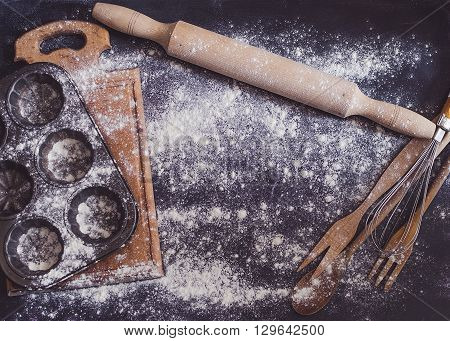 Composition of baking and kitchen accessories on black table with flour. Wooden and metal dishes cookware kitchenware. Different support stuff. Baking preparation concept. Top view. Copy space.
