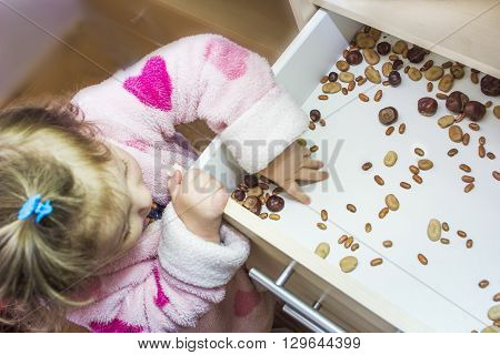 Little girl and various seeds in a drawer
