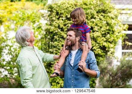 Smiling granddad looking at son carrying grandson in yard