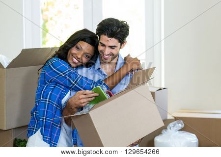 Young couple embracing while unpacking carton boxes in new house