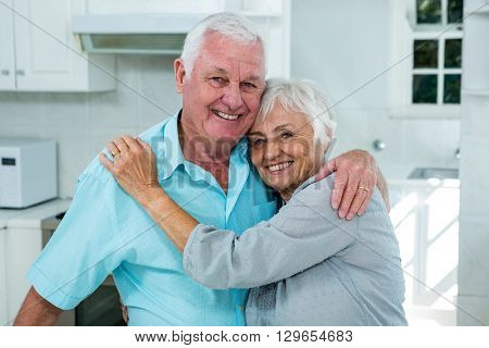 Portrait of affectionate senior couple embracing at home