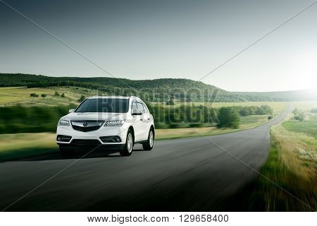 Saratov, Russia - August 11, 2015: Modern car Acura MDX fast drive on asphalt road at sunset