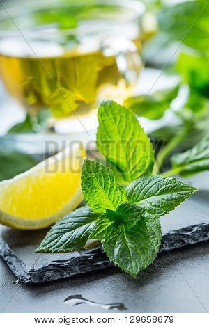 Mint leaf. Mint leaves. Tea. Mint Tea. Herbal tea. Tea in a glass cup mint leaves dried tea sliced lime. herbs tea and mint leaves on a slate plate in a restaurant or teahouse tea room.