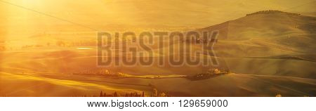 Wavy fields in Tuscany at sunet, Italy. Natural outdoor seasonal autumn background with sun shining. Panoramic view.