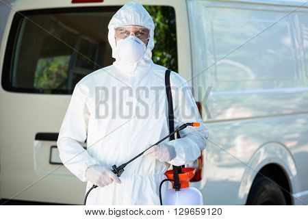 Portrait of pest control man standing behind a van