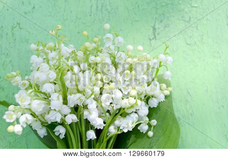 Beautiful lilies of the valley on old wooden background. Bouquet of lilies of the valley.