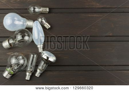 Different types and shapes of incandescent light bulbs on a wooden background. Sales of light bulbs. Advertising for lighting equipment.