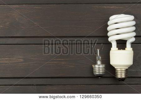 Broken incandescent bulbs and new energy-saving light bulb on wooden background. Sales of light bulbs. Advertising on lighting technology.