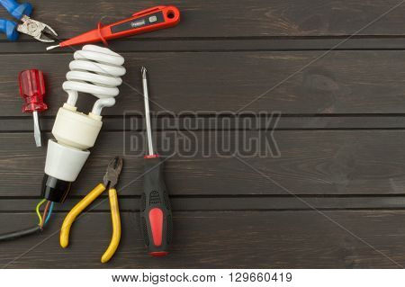 Repair broken lights. Energy saving light bulb on a dark background. Sales of light bulbs. Advertising on lighting technology. Eletro desk technician.
