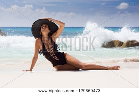 Beautiful, sexy woman in black swimming dress and straw sunhat