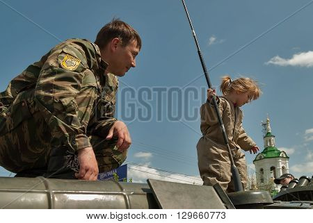 Tyumen, Russia - June 1, 2008: Children's Day. Special forces police department demonstrates BTR-82A armoured personnel carrier for children. Little girl stands on vehicle. Pioneer Palace of Arts