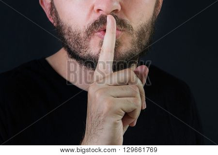 Serious man with beard and mustache making silence gesture, pst, shh, face detail