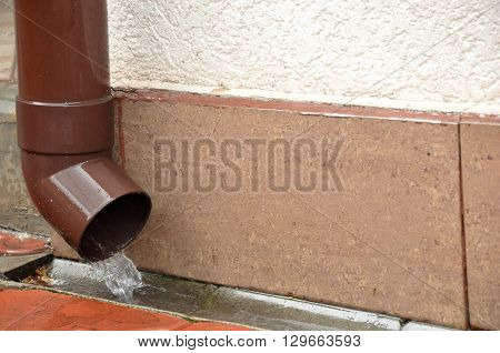 Water flow from the drainpipe installed on the wall