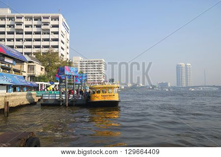 BANGKOK, THAILAND - JANUARY 24, 2014: Stop river bus on the Chao Phraya river. The tourists disembark from the water bus on the river