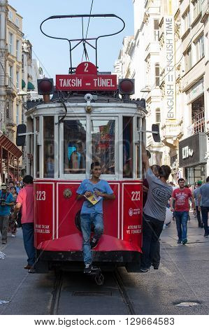 ISTANBUL TURKEY - JULY 31 2015 : The Taksim Tunel Nostalgia Tram trundles along the istiklal street and people at istiklal avenue