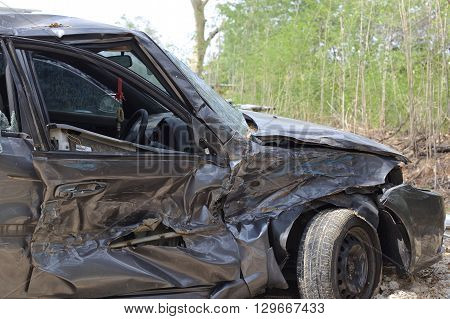 A wrecked car lays in wait after a vicious car accident. Rescue workers linger in the background.