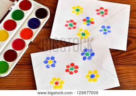 Two drawings with flowers, finger painting, children game. Colorful paint. Brown wooden background