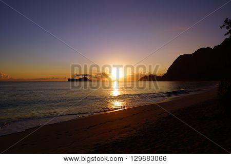 Early Morning Sunrise on Waimanalo Beach on Oahu Hawaii over Rock Island bursting through the clouds. 2013.