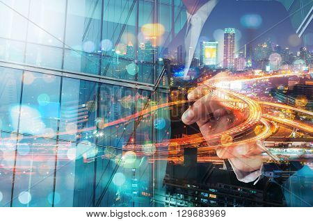 Double Exposure Of Businessman Draw Something With City Traffic Scene At Night