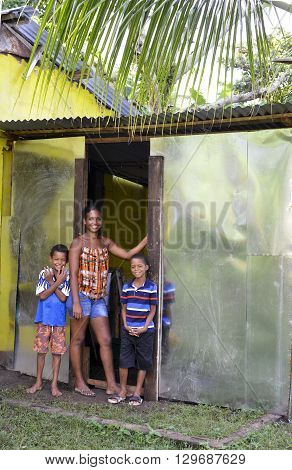 BIG CORN ISLAND NICARAGUA-NOV. 16: A proud young mother and two boys are seen by new zinc sheet metal house in jungle in Big Corn Island Nicaragua Central America on November 16 2015.
