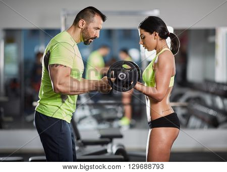 Trainer Helping With Biceps Curl