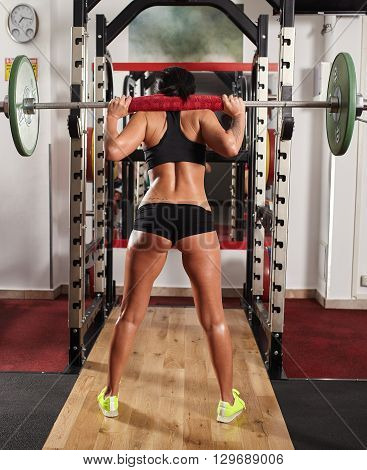 Woman Doing Squats With Barbell On Neck
