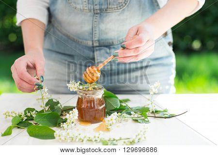 Honey dripping from a wooden honey dipper in a jar. Female hands holding wooden honey dipper.