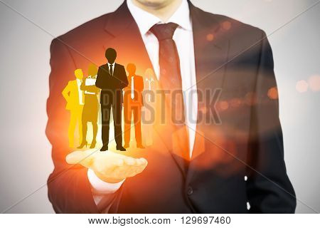 Human resources concept with man in suit holding bright orange businesspeople silhouettes