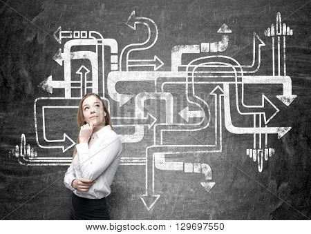 Different direction concept with thoughtful businesswoman next to chalkboard with arrows sketch