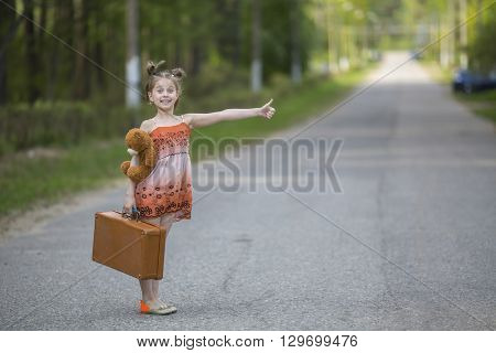 Funny little girl hitchhiker with a suitcase and a teddy bear.