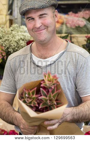 London, England - May 8, 2016: Stall holder selling a bunch of flowers at Columbia Road Flower Market. UK