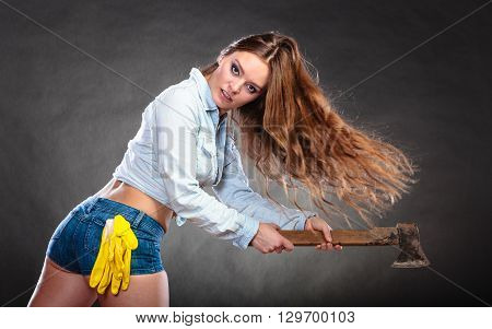 Sexy seductive woman holding axe chopper. Strong girl feminist working in man profession. Independent female. Studio shot.