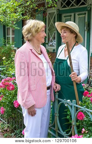 Two Senior Women Talking Together In Garden