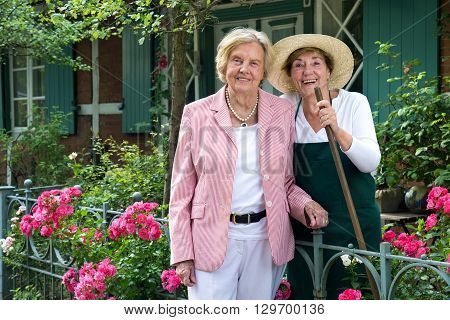 Two Senior Women Standing Together In Garden