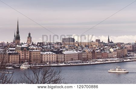 Vintage tinted snapshoot  Winter view over strait of Stockholm downtown. Boat onth water. Sweden