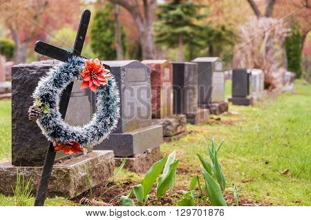 Funeral wreath with red flowers on a cross in a cemetary with many headstones in the background. poster