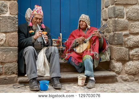 CUSCO, PERU - NOVEMBER 26 2011: Two peruvian blind men with traditional clothes playing flute and mandoline in the street of Cusco Peru