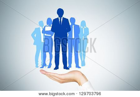 Human resources concept with man's hand holding businesspeople silhouettes
