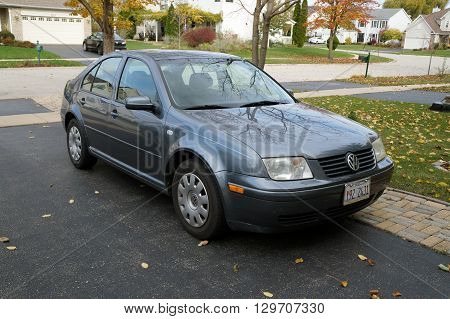 JOLIET, ILLINOIS / UNITED STATES - NOVEMBER 5, 2015: A Volkswagen Jetta is parked in the driveway of a home in Joliet, Illinois.
