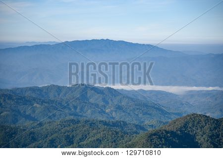 Beautiful blue-green layers of tropical mountain range landscape from top view in majestic fog of winter
