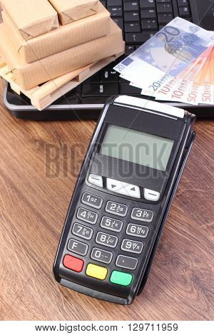 Credit card reader payment terminal with currencies euro laptop and small wrapped boxes on wooden pallet cashless or cash paying for products and shipping