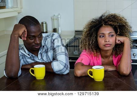 Upset couple ignoring each other after fight at home