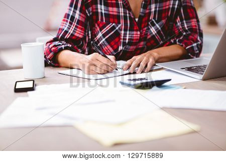 Midsection of woman writing in notepad while sitting at table