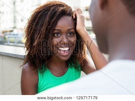 Laughing african girl flirting with friend in the city